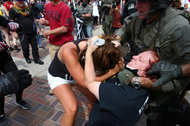 Police intervene as two women fight at a pro-law enforcement rally that clashed with counter protesters demonstrating against racial inequality, in Denver, Colorado, U.S. July 19, 2020. (Photo by Kevin Mohatt/Reuters)