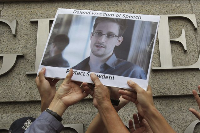 Protesters supporting Edward Snowden, a contractor at the National Security Agency (NSA), hold a photo of Snowden during a demonstration outside the U.S. Consulate in Hong Kong June 13, 2013. China's Foreign Ministry offered no details on Thursday on Snowden, the National Security Agency contractor who revealed the U.S. government's top-secret monitoring of phone and Internet data and who is in hiding in Hong Kong. (Photo by Bobby Yip/Reuters)