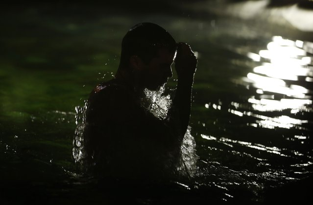 A man immerses himself in icy water during celebrations for Russian Orthodox Epiphany in Moscow January 19, 2015. (Photo by Maxim Zmeyev/Reuters)