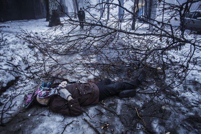 A person walk near the remains of a man lying near a bus stop that was damaged in shelling by the Ukrainian army in Donetsk, eastern Ukraine, Tuesday, January 20, 2015. At least three civilians were killed in shelling Tuesday in eastern Ukraine as fighting continued between government and rebel forces in the separatist-held city of Donetsk. (Photo by Manu Brabo/AP Photo)