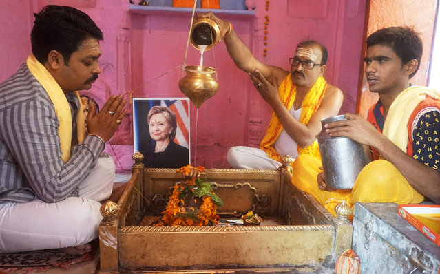 Indian devotees perform a prayer with a photograph of US Presidential candidate Hillary Clinton at a temple in Varanasi on November 7, 2016, ahead of voting in the US Presidential elections. Top musicians from Bruce Springsteen to Beyonce to Madonna are rallying behind Hillary Clinton in the countdown to the November 8 election, adding A-list star power to a massive get-out-the-vote operation. (Photo by AFP Photo/Stringer)