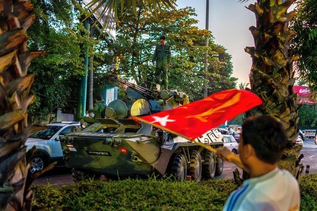 """A man waves a red National League For Democracy (NLD) flag near a broken-down military armored vehicle on February 14, 2021 in Yangon, Myanmar. The U.S. Embassy in Myanmar told Americans in Myanmar to """"shelter in place"""" in an announcement after military movements and reports of possible interruptions to telecoms. Armored vehicles were seen on the streets of Myanmar's capital, and telecoms companies said they had been ordered to suspend services between 1 AM and 9 AM on Monday. (Photo by Hkun Lat/Getty Images)"""