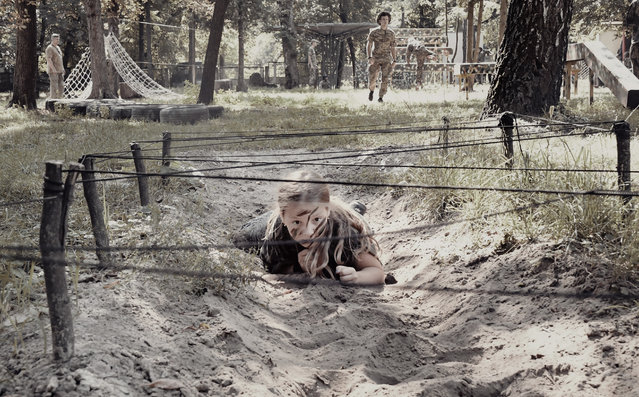 A girl crawls under wire during paramilitary training at a patriotic youth camp. (Photo by Aude Osnowycz/The Guardian)