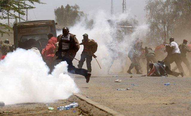 Demonstrators run in a cloud of teargas after riot policemen dispersed them during protests to oust Narok county Governor Samuel Tunai in Narok, Kenya, January 26, 2015. (Photo by Thomas Mukoya/Reuters)