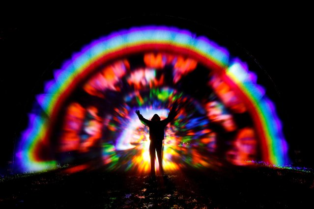"""A person gestures while interacting with Artist Benjamin Clegg's """"Rainbow in the Dark"""" at Light Up Trails at The Wiston Estate, amid the spread of the coronavirus disease (COVID-19), in Steyning, West Sussex, Britain, December 9, 2020. (Photo by Paul Childs/Reuters)"""