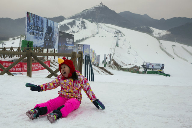 In this photo taken Saturday, January 24, 2015, a child makes a face while having her photo taken with the snow covered slopes of the Nanshan ski resort behind her in Beijing. As Beijing makes a final push in its bid for the 2022 Winter Olympics, Chinese President Xi Jinping says winning the bid will encourage over 300 million Chinese to take up winter sports by 2022, according to state-run Xinhua News agency. (Photo by Ng Han Guan/AP Photo)