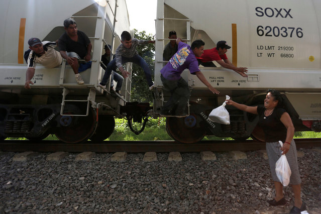 "A woman from a group called ""Las Patronas"" (The bosses), a charitable organization that feeds Central American immigrants who travel atop a freight train known as ""La Bestia"", passes food and water to immigrants on their way to the border with the United States, at Amatlan de los Reyes, in Veracruz state, Mexico October 22, 2016. (Photo by Daniel Becerril/Reuters)"