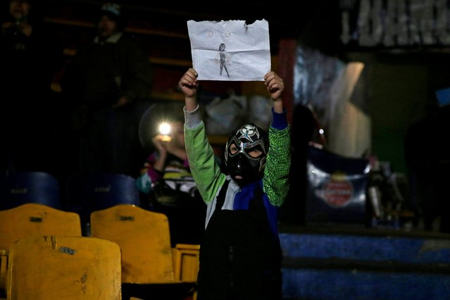 A child spectator holds a drawing portraying a wrestler known as Toxico during an extreme wrestling fight at the Arena Neza on the outskirts of Mexico City, Mexico October 28, 2016. (Photo by Carlos Jasso/Reuters)