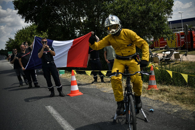 Firefighters in their working outfit wave a French flag as they cheer during the fourth stage of the 105th edition of the Tour de France cycling race between La Baule and Sarzeau, western France, on July 10, 2018. (Photo by Marco Bertorello/AFP Photo)