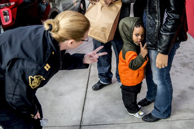 Flint Police Capt. Leigh Golden, left, holds up two fingers as to mimic Israel Altheimer, 2, as he tells her his age on Thursday, December 10, 2015 at the Flint Farmers' Market in Flint, Mich This is the second year The Flint Police Department teamed up with the Salvation Army of Flint and Genesee County to help raise donations for the Red Kettle Drive. (Photo by Jake May/The Flint Journal-MLive.com via AP Photo)