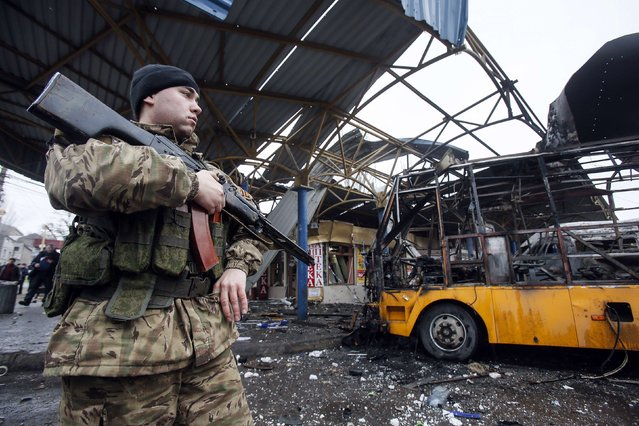A member of the armed forces of the separatist self-proclaimed Donetsk People's Republic stands guard near a destroyed vehicle at a bus station after shelling in Donetsk, February 11, 2015. At least one person was killed on Wednesday when a shell hit a bus station in the centre of rebel-controlled Donetsk city, east Ukraine, a Reuters witness said. (Photo by Maxim Shemetov/Reuters)