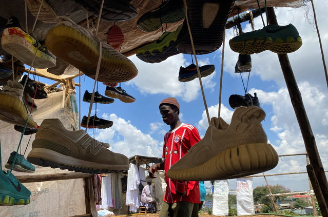 A vendor arranges second-hand shoes for sale at an open stall during Good Friday, after the government banned gatherings amid concerns about the spread of coronavirus disease (COVID-19) at the Kibera slums in Nairobi, Kenya on April 2, 2021. (Photo by Thomas Mukoya/Reuters)