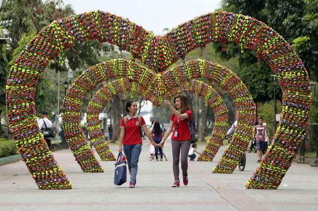 Filipinos walk past a flower heart installation on the eve of Valentine's Day in a Park in Manila, Philippines, 13 February 2015. Valentine's Day is celebrated all over the world on 14 February, with lovers expressing their love for each other in such ways as sending cards and giving flowers. (Photo by Ritchie B. Tongo/EPA)