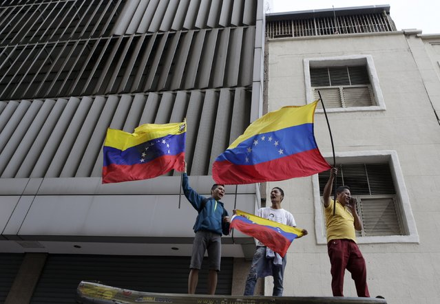 Supporters of Venezuela's opposition hold national flags as they stand some streets away from the building housing the National Assembly in Caracas, January 5, 2016. (Photo by Marco Bello/Reuters)
