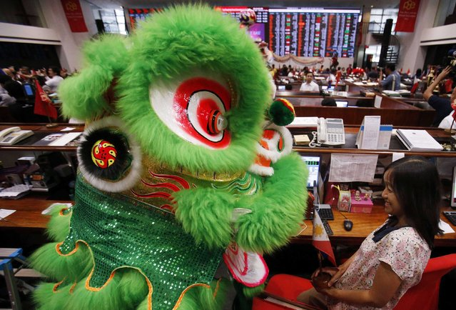 A lion dancer approaches a trader, as part of Chinese Lunar New Year celebrations, on the floor of the Philippine Stock Exchange in Manila's Makati financial district, February 18, 2015. (Photo by Erik De Castro/Reuters)