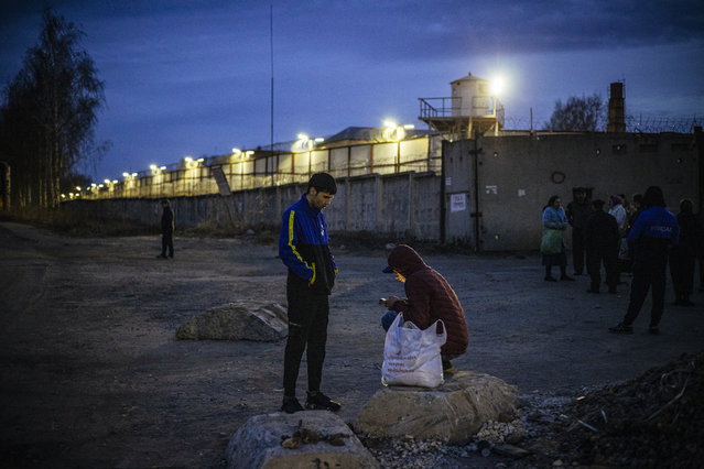 """Migrant workers stand by the barbed wire fence of the IK-3 penal colony where jailed Kremlin critic Alexei Navalny was reportedly transferred in the city of Vladimir on April 19, 2021. Russia's penitentiary service said on April 19, 2021, it was transferring ailing Kremlin critic Alexei Navalny to a prison hospital, as the EU warned it would hold Moscow responsible for the state of his health. The United States on Sunday threatened Russia with """"consequences"""" if President Vladimir Putin's major domestic opponent – who launched a hunger strike three weeks ago – dies in jail, with Navalny's private doctors warning at the weekend he could pass away at """"any minute"""". (Photo by Dimitar Dilkoff/AFP Photo)"""