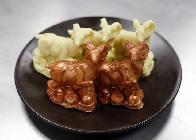 Goat-shaped chocolates, two of them painted with edible gold powder, displayed on a plate while a chef prepares to make a cake celebrating the upcoming Chinese Lunar New Year, during a photo opportunity at a kitchen of Kerry Hotel in Beijing, February 12, 2015. (Photo by Kim Kyung-Hoon/Reuters)