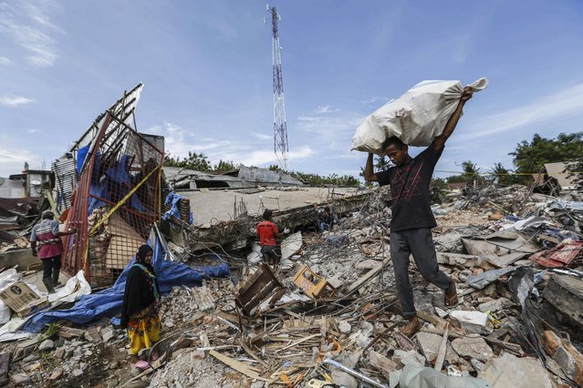 Indonesian villagers collect useable belongings from their collapsed building after an earthquake struck Pidie Jaya, Aceh, Indonesia, 07 December 2016. (Photo by Hotli Simanjuntak/EPA)