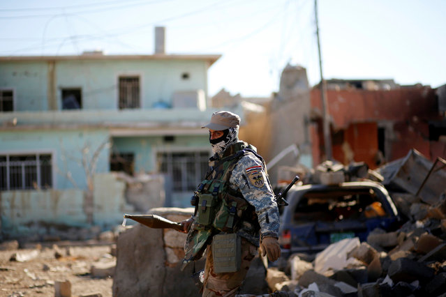 An Iraqi soldier carries a RPG as he walks among wreckage of buildings damaged from clashes in the frontline during a battle with Islamic State militants in the neighbourhood of Intisar, eastern Mosul, Iraq, December 6, 2016. (Photo by Ahmed Jadallah/Reuters)