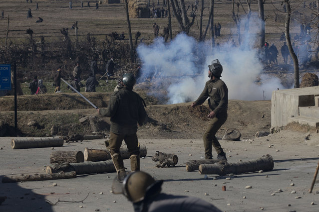 An Indian police man throws stones at Kashmiri Muslim protesters as they clash  in Naina village some 40 kilometers (25 miles) south of Srinagar, Indian controlled Kashmir, Wednesday, January 20, 2016. Violent clashes between police and protesters erupted Wednesday in Indian-controlled Kashmir, leaving a man dead and two others wounded, officials said. (Photo by Dar Yasin/AP Photo)
