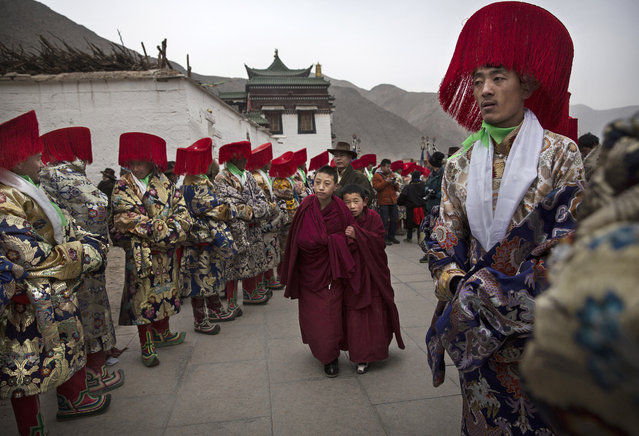 Two young Tibetan Buddhist monks of the Gelug, or Yellow Hat order, walk passed men in traditional clothing before a procession during Monlam or the Great Prayer rituals on March 4, 2015 at the Labrang Monastery, Xiahe County, Amdo, Tibetan Autonomous Prefecture, Gansu Province, China. (Photo by Kevin Frayer/Getty Images)