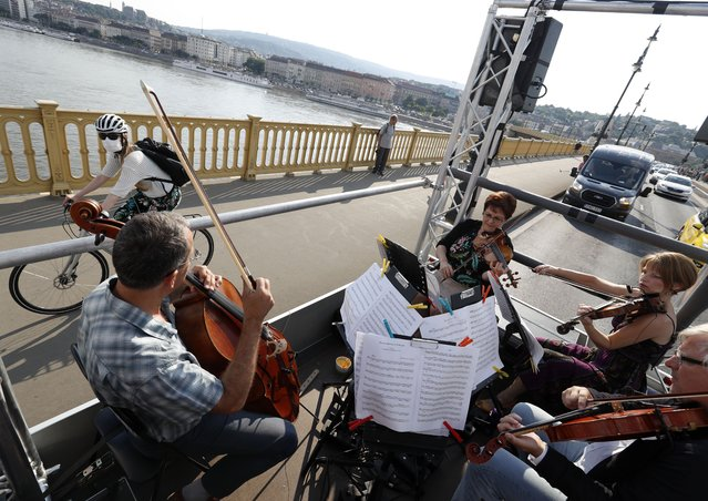 Members of the Budapest Festival Orchestra play music on the back of a truck while driving through downtown Budapest, Hungary, Wednesday June 9, 2021. The prestigious orchestra, founded and led by renowned composer Ivan Fischer, took to the streets as five members of the orchestra performed classical music to motorists and passers-by. The musical parade was aimed at encouraging Hungarians to start returning to live performances in concert halls as the pandemic wanes, after more than a year in which people were homebound and forced to take in their culture online. (Photo by Laszlo Balogh/AP Photo)