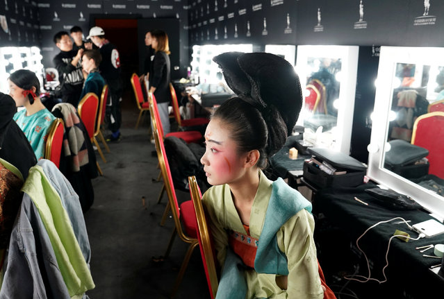A performer rests backstage before a show by designer Chu Yan at China Fashion Week in Beijing, China, October 30, 2018. (Photo by Jason Lee/Reuters)