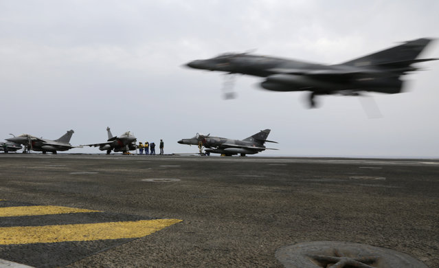 In this Tuesday, March 17, 2015 photo, a French military plane lands on the flight deck of the French Navy aircraft carrier Charles de Gaulle in the Persian Gulf. (Photo by Hasan Jamali/AP Photo)