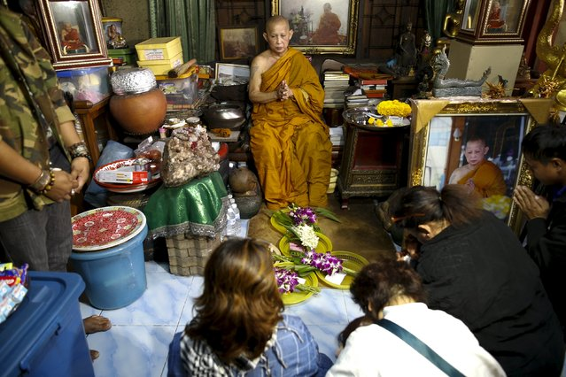 "Buddhist monk Phra Winai Thidtapanyo (C), 64, blesses devotees who brought ""child angel"" dolls during a blessing ritual at Wat Bua Khwan temple in Nonthaburi, Thailand, January 26, 2016. (Photo by Athit Perawongmetha/Reuters)"