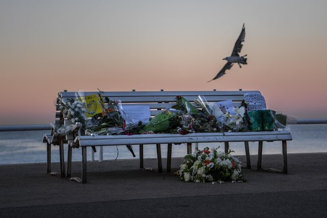 A tribute is laid on a bench where a person was killed on the Promenade des Anglais on July 17, 2016 in Nice, France. Six people believed to be linked to the man who killed 84 people in Nice are in police custody according to a statement by the Paris prosecutor's office after a French-Tunisian attacker killed 84 as he drove a lorry through crowds, gathered to watch a firework display during Bastille Day Celebrations. The attacker then opened fire on people in the crowd before being shot dead by police. (Photo by David Ramos/Getty Images)