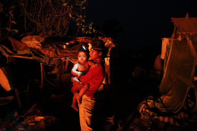 Saray, 23-year-old woman wearing a head torch holds her one-year-old daughter Phearom after working at a landfill dumpsite outside Siem Reap March 18, 2015. Saray moved to the dumpsite five years ago after marrying a man who lives there. She makes $2 per day collecting usable items at the dumpsite. (Photo by Athit Perawongmetha/Reuters)