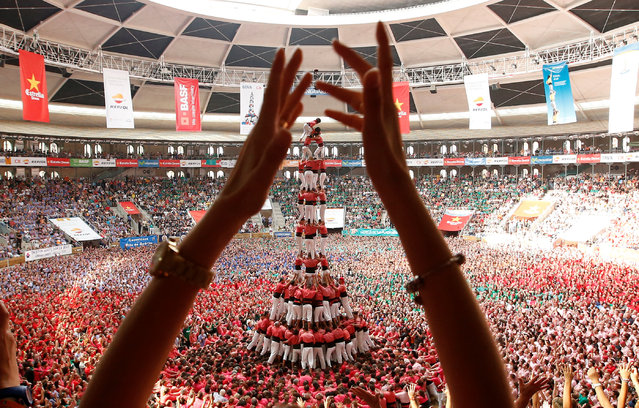 """SPAIN: Colla Vella Xiquets de Valls form a human tower called """"castell"""", while a supporter applauds, during a biannual competition in Tarragona city, Spain, October 2, 2016. (Photo by Albert Gea/Reuters)"""