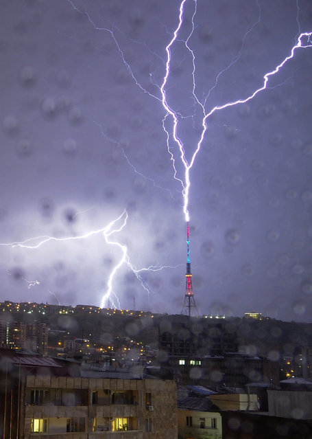 In this photo taken through a window covered with raindrops, lightning hits a TV tower in Yerevan, the capital of Armenia, Sunday, October 4, 2020. (Photo by Dmitri Lovetsky/AP Photo)
