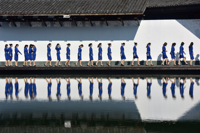 Attendants for the fifth World Internet Conference (WIC) are seen reflected in the water during a group photo session outside the venue, in Wuzhen town of Jiaxing, Zhejiang province, China on November 8, 2018. (Photo by Reuters/China Stringer Network)