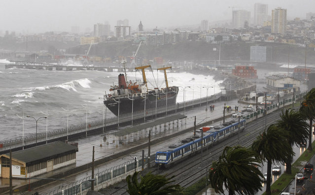 Waves batter a merchant vessel stranded along the coast during a heavy storm in Valparaiso City, northwest of Santiago, Chile, July 6, 2010. (Photo by Eliseo Fernandez/Reuters)