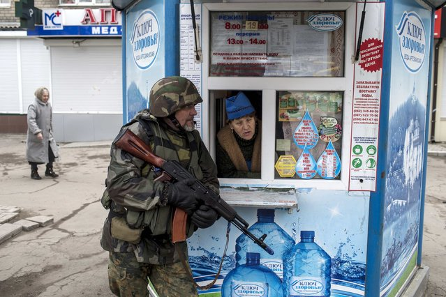 A pro-Russian rebel takes cover as a woman from inside a kiosk looks on, during what the rebels said was an anti-terrorist drill in Donetsk, March 18, 2015. (Photo by Marko Djurica/Reuters)