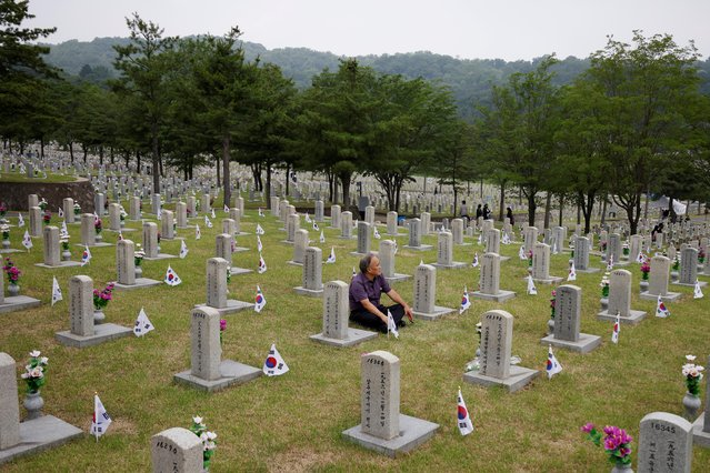 A man sits next to a gravestone of a family member who died for the country, on Korean Memorial Day at the National Cemetery in Seoul, South Korea, June 6, 2021. (Photo by Kim Hong-Ji/Reuters)