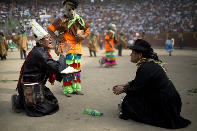 In this Sunday, March 29, 2015 photo, dance troupers, one dressed as a priest, and another dressed as a policeman, act out the detention of a woman during the Vencedores de Ayacucho dance festival, in the Acho bullring in Lima, Peru. (Photo by Rodrigo Abd/AP Photo)