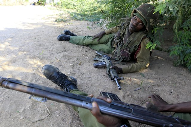 A Kenya Defense Force soldier takes cover near the perimeter wall where attackers are holding up at a campus in Garissa April 2, 2015. (Photo by Noor Khamis/Reuters)