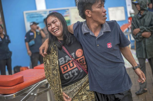 A woman reacts after identifying a relative among the bodies of tsunami victims in Carita, Indonesia, Sunday, December 23, 2018. The tsunami occurred after the eruption of a volcano around Indonesia's Sunda Strait during a busy holiday weekend, sending water crashing ashore and sweeping away hotels, hundreds of houses and people attending a beach concert. (Photo by Fauzy Chaniago/AP Photo)
