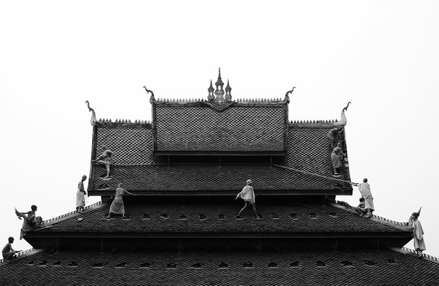 """""""Monk's Roof"""". Some students from a Monk's school in Luang Prabang, laos. They maintain the roof temple. There are so many young Monks now, that they are a part of tourism attraction. The politic peoples ask them to show them self for tourism. It's a business. Photo location: Luang Prabang, Laos. (Photo and caption by Julient Tardent/National Geographic Photo Contest)"""