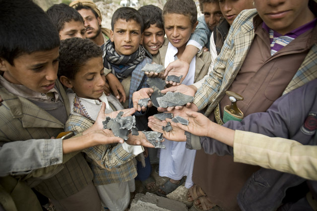 Yemeni boys display shrapnel they collected from the rubble of houses destroyed by Saudi-led airstrikes in a village near Sanaa, Yemen, Saturday, April 4, 2015. Since their advance began last year, the Shiite rebels, known as Houthis have overrun Yemen's capital, Sanaa, and several provinces, forcing the country's beleaguered President Abed Rabbo Mansour Hadi to flee the country. (Photo by Hani Mohammed/AP Photo)