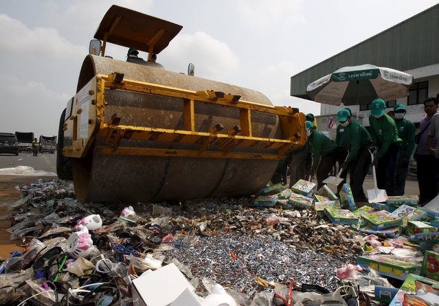 Thai Department of Intellectual Property and police officials destroy counterfeit goods with a steamroller at Khlongluang Transportation Station in Pathumtani province, on the outskirts of Bangkok April 9, 2015. (Photo by Chaiwat Subprasom/Reuters)