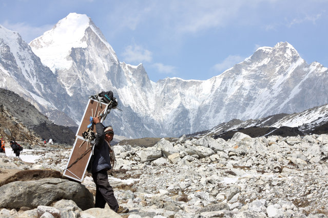 A porter carries crates containing oxygen tanks, with Mt Lingtren seen behind left, and Mt. Khumbutse, right, on his way towards Everest Base Camp, at Lobuche, Nepal, Friday, April 10, 2015. (Photo by Tashi Sherpa/AP Photo)