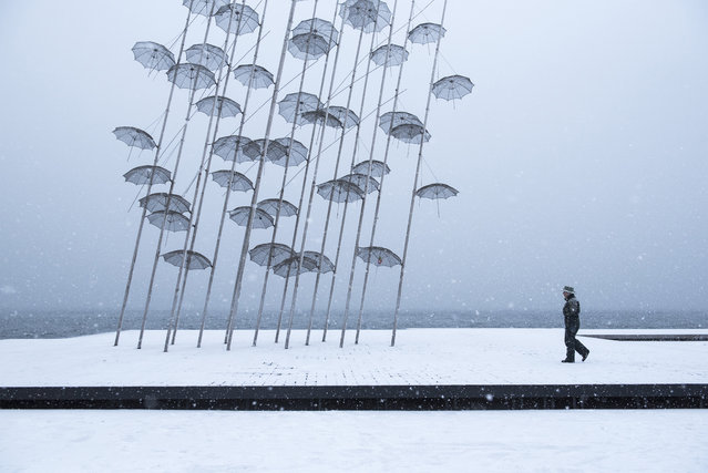 "A woman walks past ""Umbrellas"" sculpture, by George Zongolopoulos, at the seafront of the northern Greek city of Thessaloniki, on Tuesday, January 10, 2017. Snow closed hundreds of schools in the country, as added pressure on the government to speed up winter preparations for thousands of refugees living in camps around the country. (Photo by Giannis Papanikos/AP Photo)"