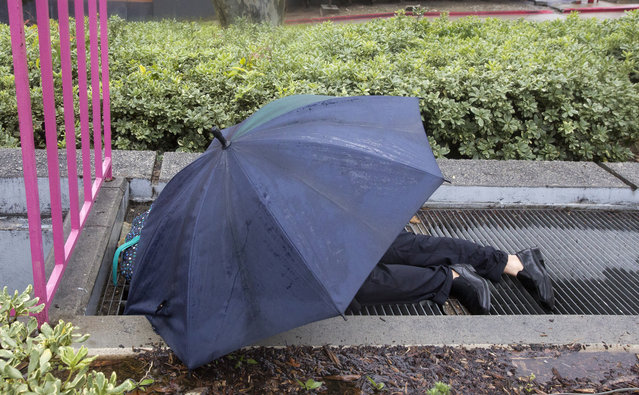 A man sleeps on top of a vent in rain at Grand Park in Los Angeles Thursday, January 17, 2019. Rain and snow fell from one end of the state to the other, canceling flights, uprooting trees, knocking down power lines and causing localized flooding. (Photo by Damian Dovarganes/AP Photo)