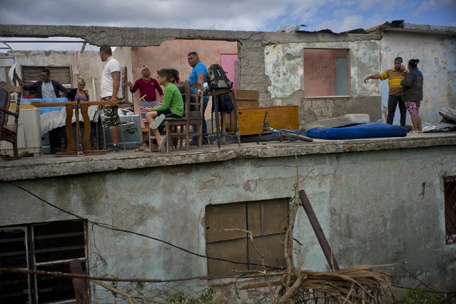 People rest in the remains of the second floor of their house, collapsed after a tornado hit Regla, Cuba, Monday, January 28, 2019. (Photo by Ramon Espinosa/AP Photo)