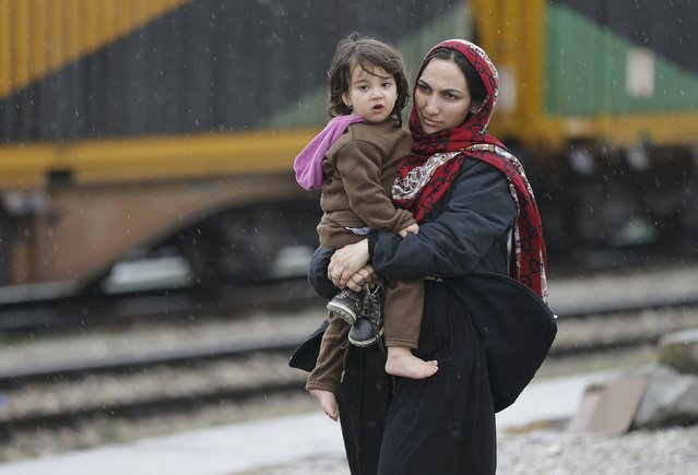 A migrant woman from Afghanistan stands with her child at the Macedonian-Serbian border near the village of Tabanovce, Macedonia February 24, 2016. (Photo by Marko Djurica/Reuters)