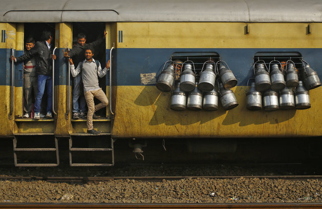 Commuters stand on the door of a passenger train as milk containers hang on the windows in Ghaziabad, on the outskirts of New Delhi, February 12, 2014. (Photo by Anindito Mukherjee/Reuters)