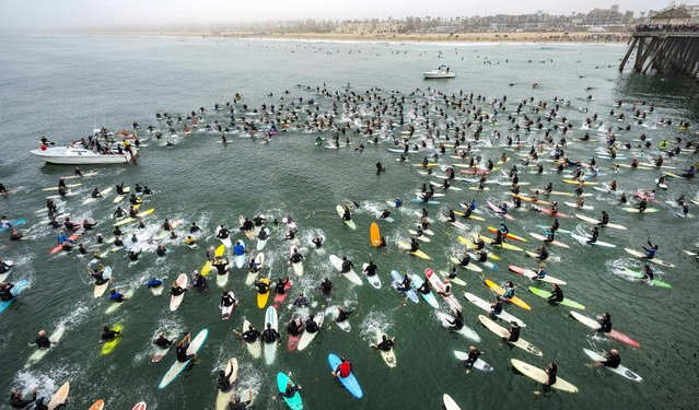 """Surfers form a circle near the end of the Huntington Beach Pier during a paddle-out for Rick """"Rockin' Fig"""" Fignetti, Saturday, August 28, 2021, in Huntington Beach, Calif. Fignetti, of Huntington Beach, was a surfer, surf shop owner and voice of surfing for many years, who died on July 16 of a heart attack. (Photo by Mark Rightmire/The Orange County Register via AP Photo)"""